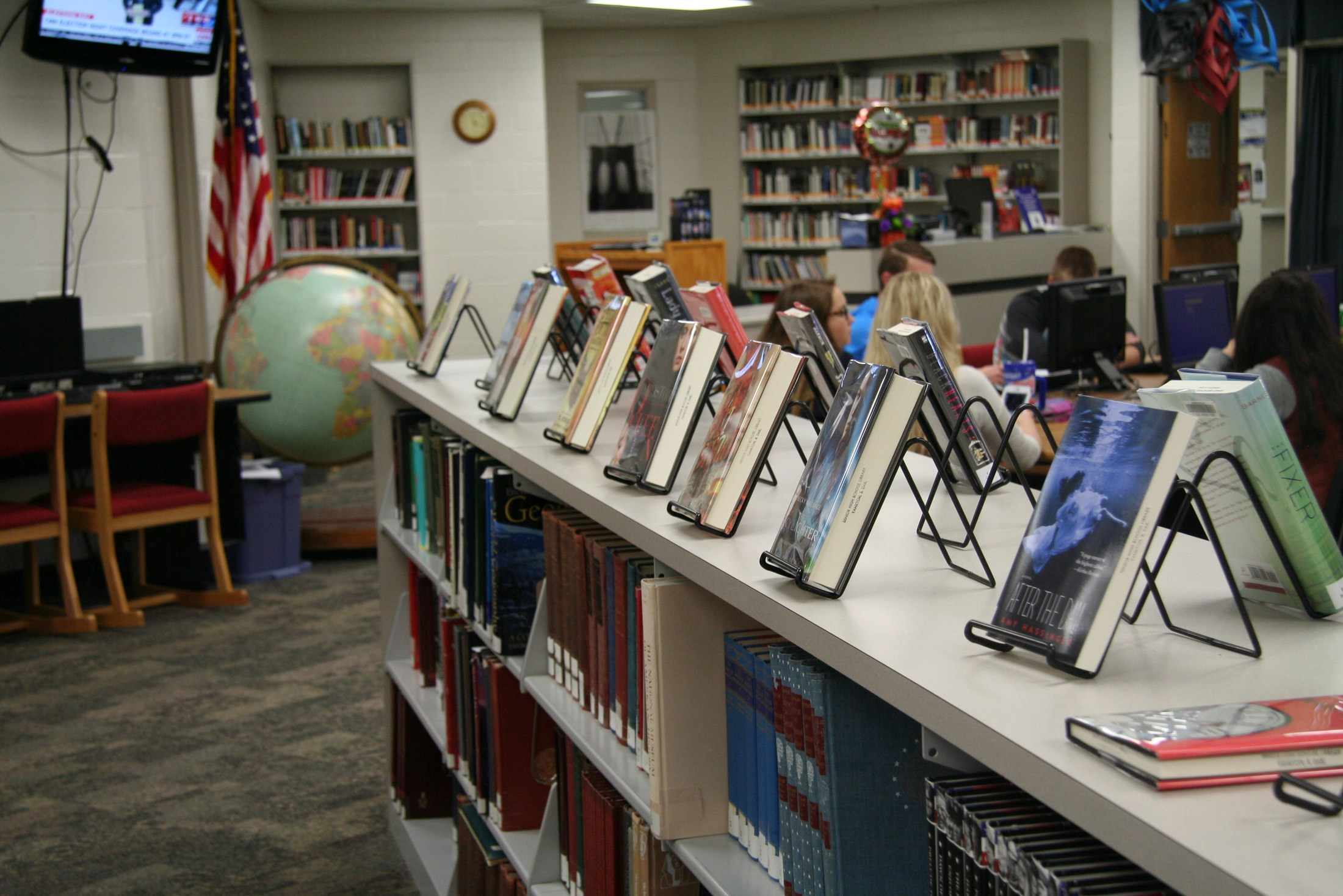 Books on shelf with students in backround