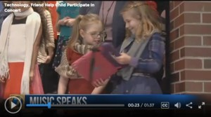 elementary student hands other student an ipad