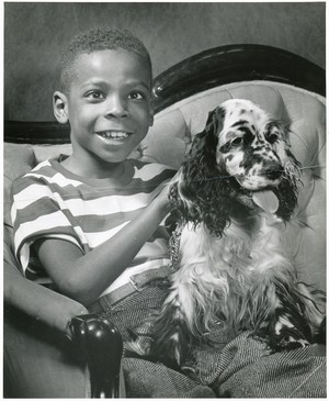 Smiling young boy with a dog on his lap.