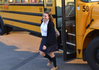 An OLSH student exits her school bus in the morning