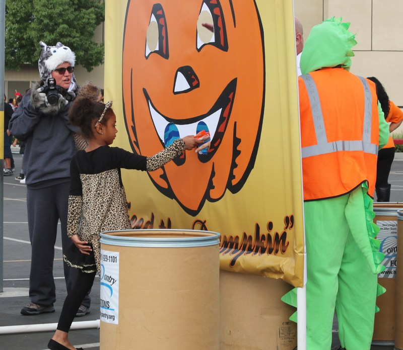 Student dropping a can into the pumpkin's mouth.