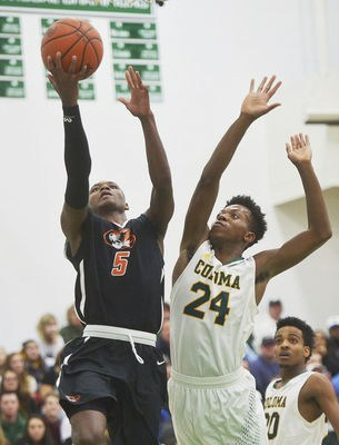 Benton Harbor's Shawn Hopkins shoots over Coloma's Michael Dancer in district action Wednesday night March 7, 2018