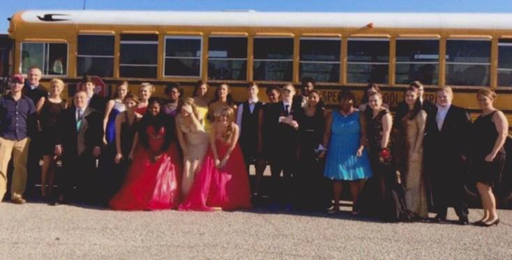 Students in formal wear in front of school bus