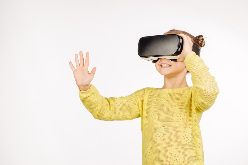 Shutterstock photo of an elementary school girl using a virtual reality appliance