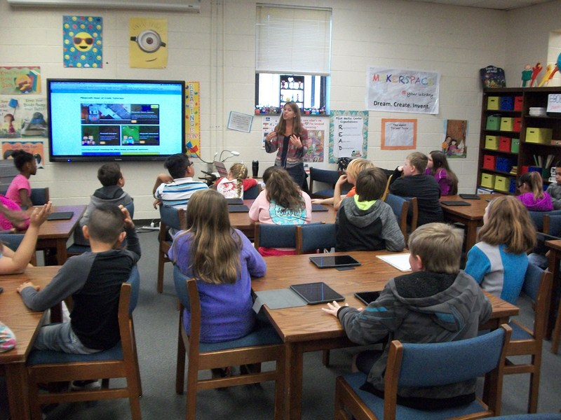 Students are working with iPads in the Media Center.