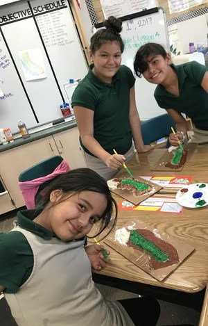 Three students work on painting their salt maps of California