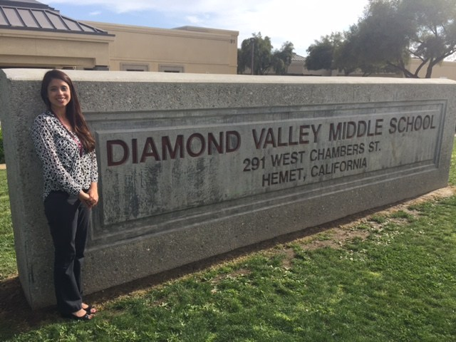 Raquel Careera in front of a Diamond Valley sign.