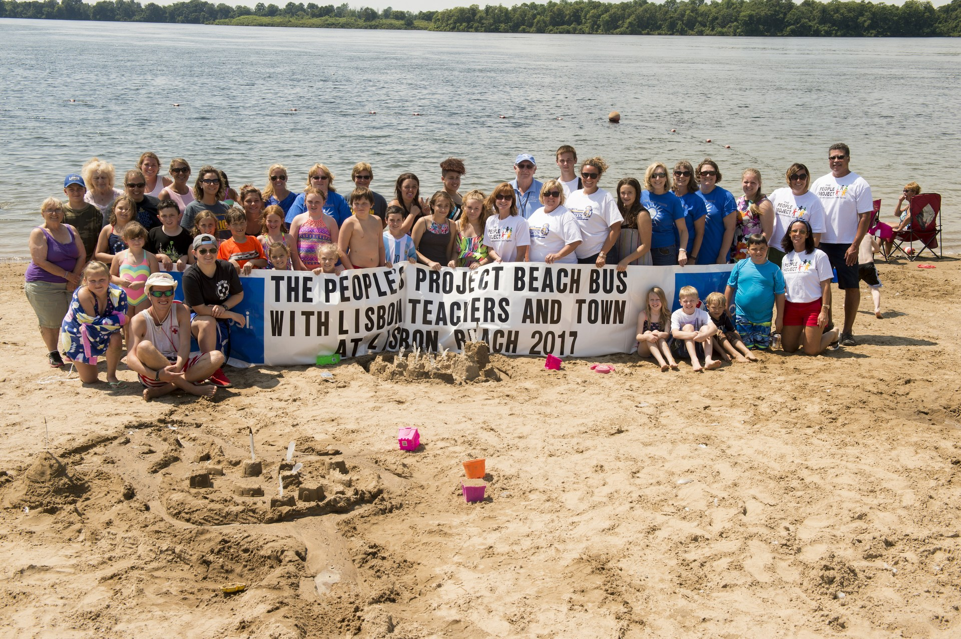 large group of adults and kids standing together on a beach