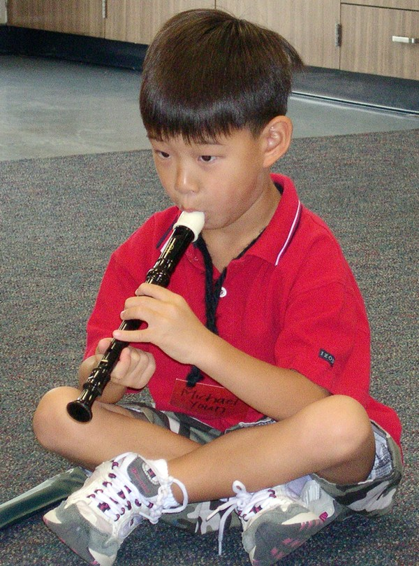A boy plaing a recorder.