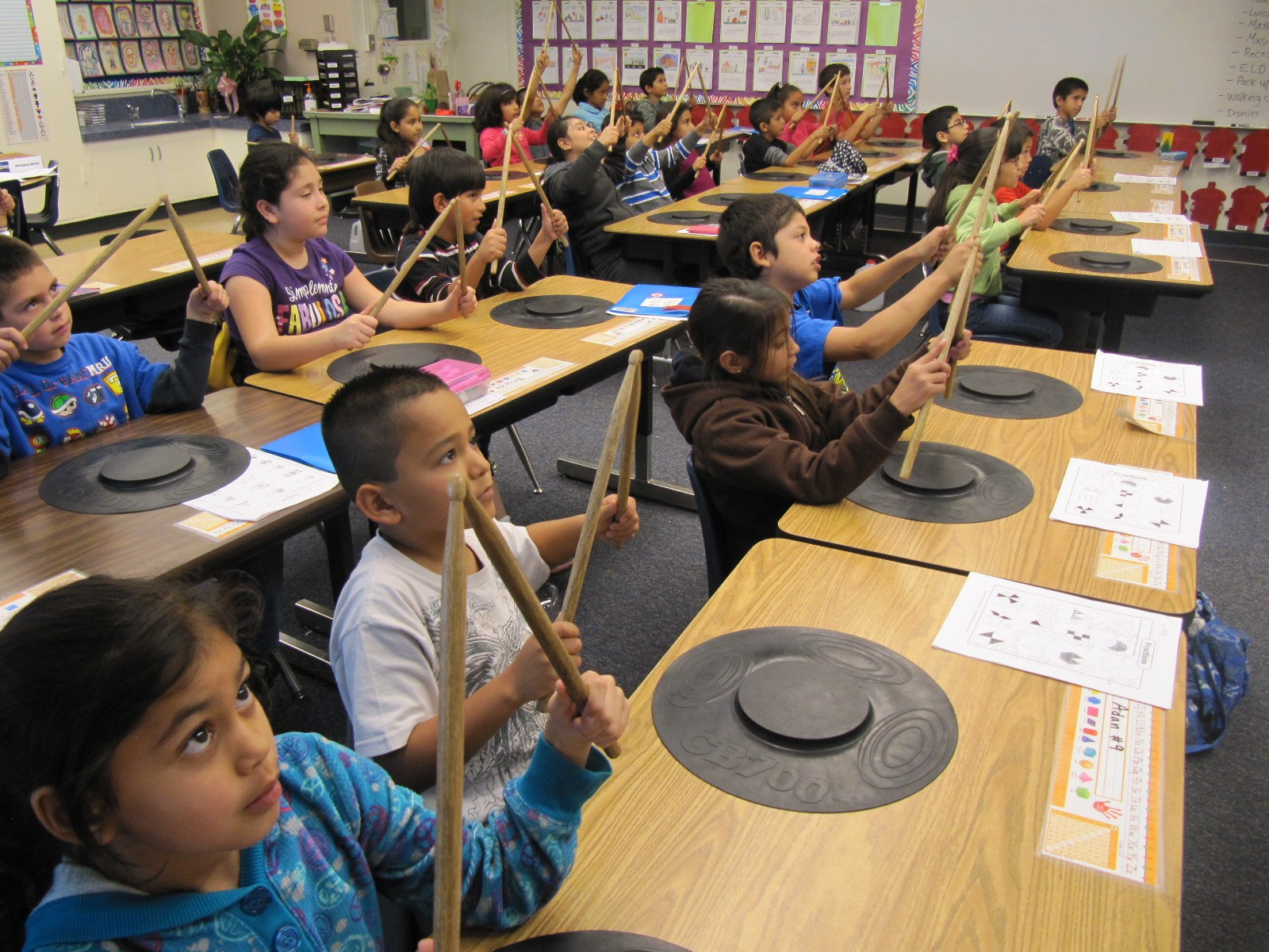 Students playing a drum pad with drum sticks in a classroom.