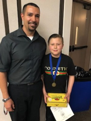 justin castillo poses with teacher robert flores wearing medal