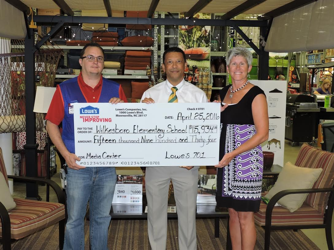 Principal and Media Specialist being presented a check for the library