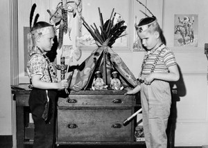 two boys wearing an indian headress and standing in fron of teepee model