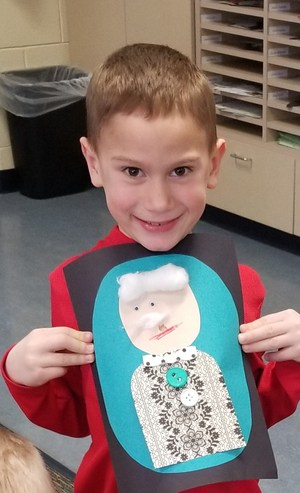 A student holds up his picture he created of what he'll look like at 100 years old.