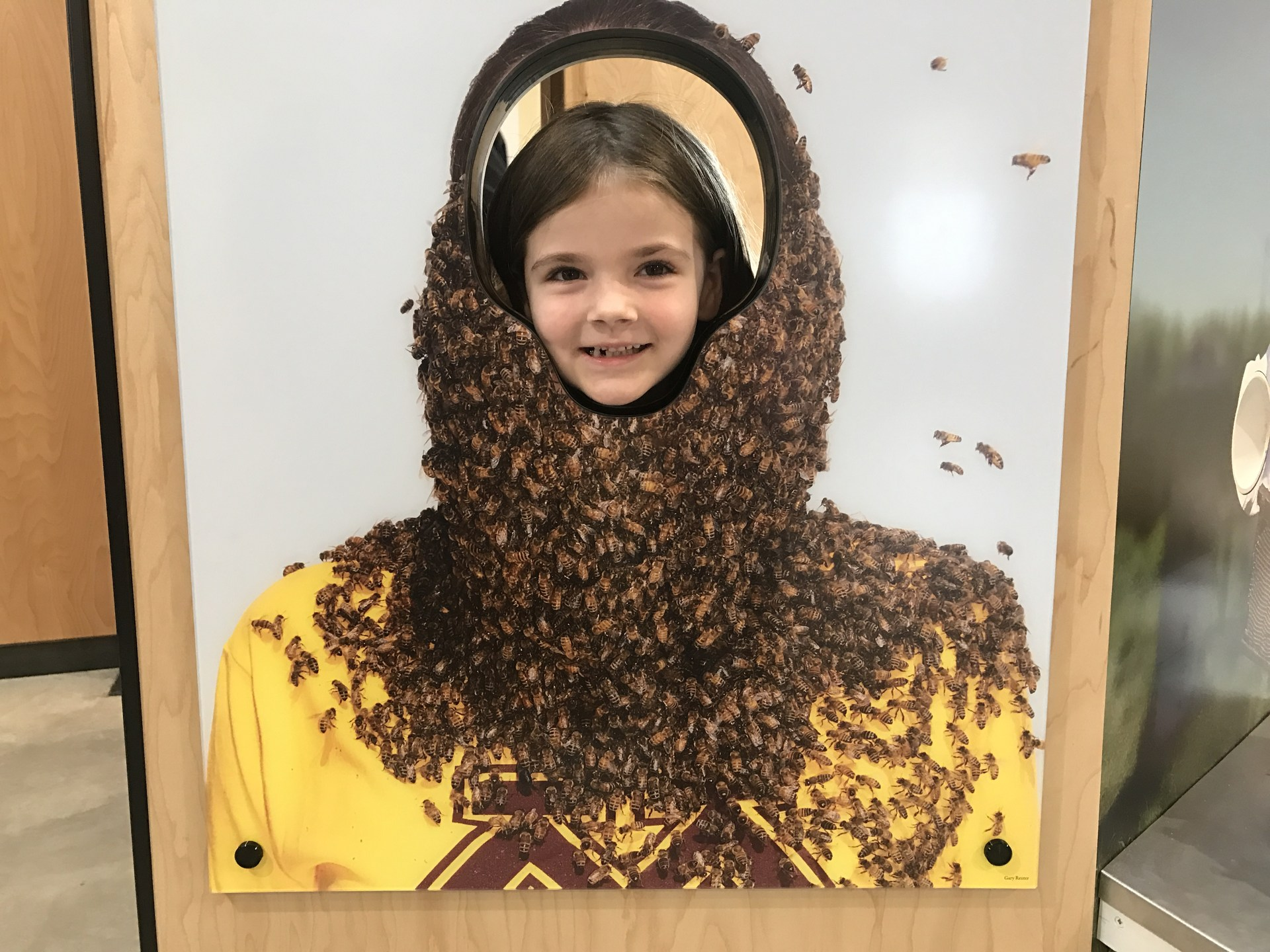 student standing in front of a bee hive