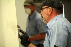 Maintenance workers finish the dry wall at a new storage room they are constructing at the old John Colemon School.
