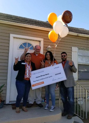 Alyssa Garza and UT officials holding a large check and balloons.