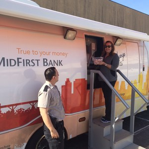 Mrs. Bell adding coins to MidFirst Coin Van