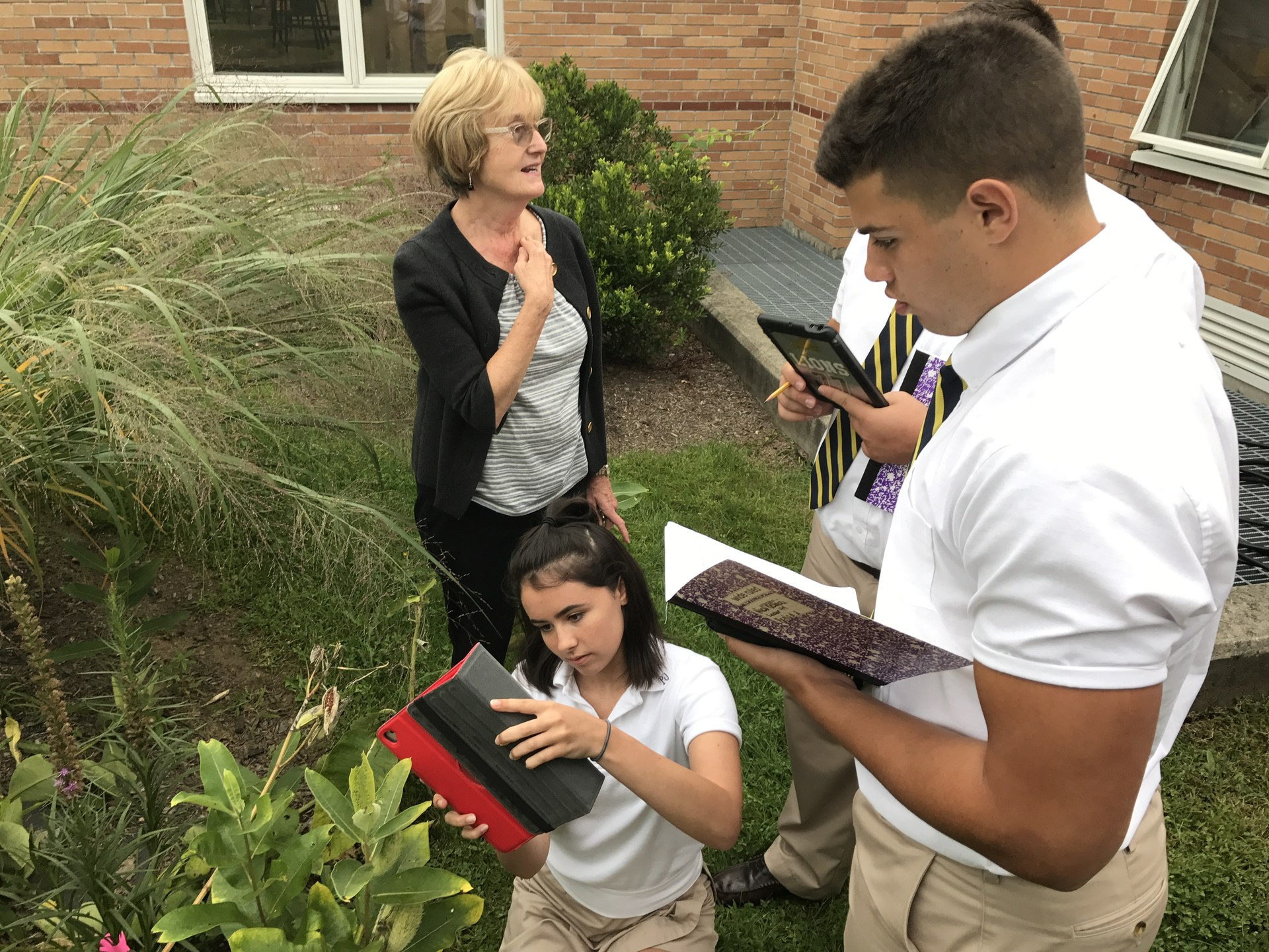 Students examining monarch butterflies outside