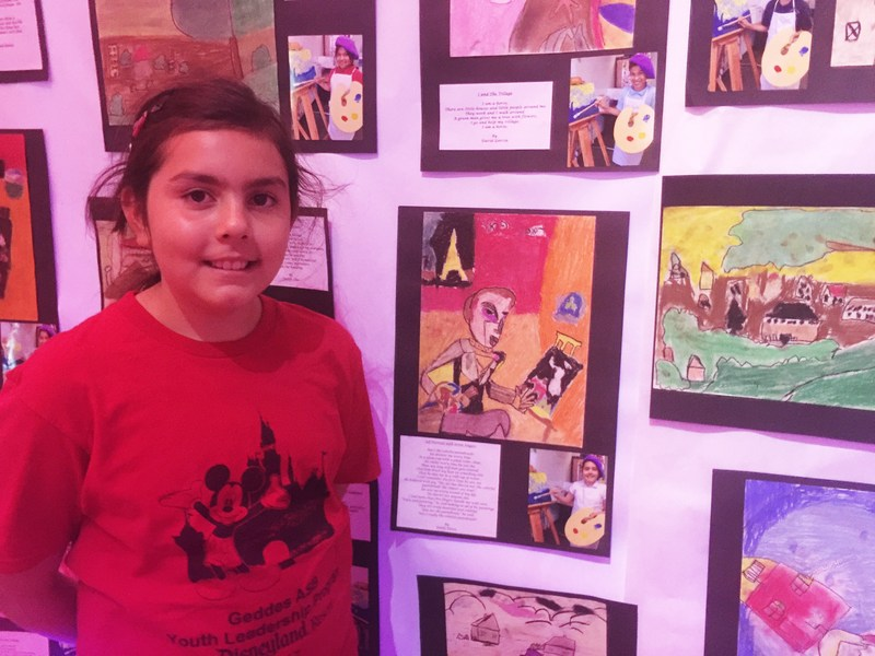 Geddes Elementary fourth-grader Emily Torres stands next to her interpretation of a Chagall self-portrait displayed with a poem she wrote from the perspective of a paintbrush during an April 12 art gallery celebrating a yearlong effort to integrate arts into core curriculum at two Baldwin Park Unified elementary schools.