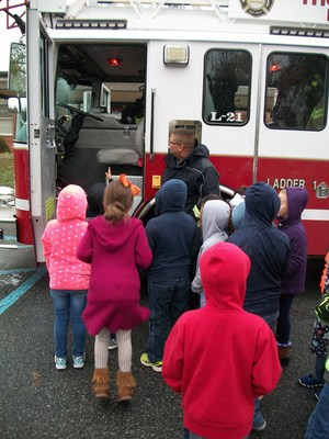 Students are looking into the cab of a fire truck as a fireman describes what is inside.