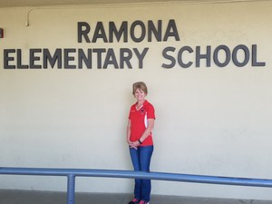 Melissa Saldana in front of the Ramona Elementary School sign