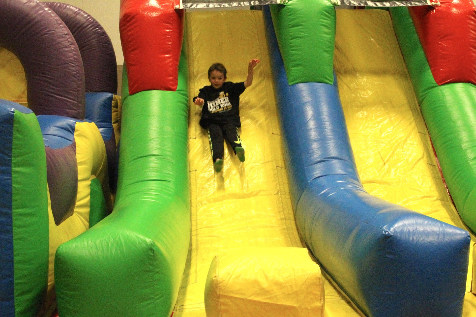 student going down inflatable slide