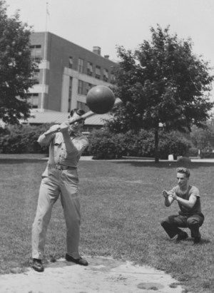 Soldiers playing baseball with a bat and basketball.