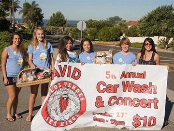 PVHS AVID students pose with car wash banner at Car Wash and Concert