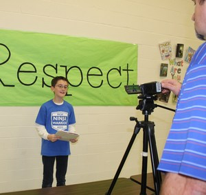 Coleman Elementary fifth grader participates in a video taped interview discussing his winning entry in the