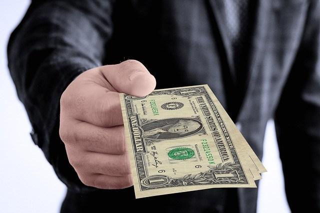 man extending hand with dollar bills