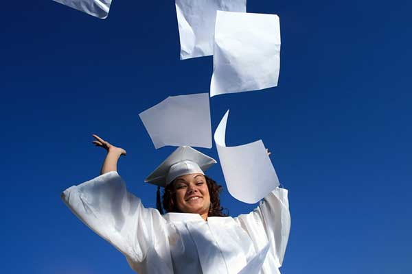 A graduate throwing papers