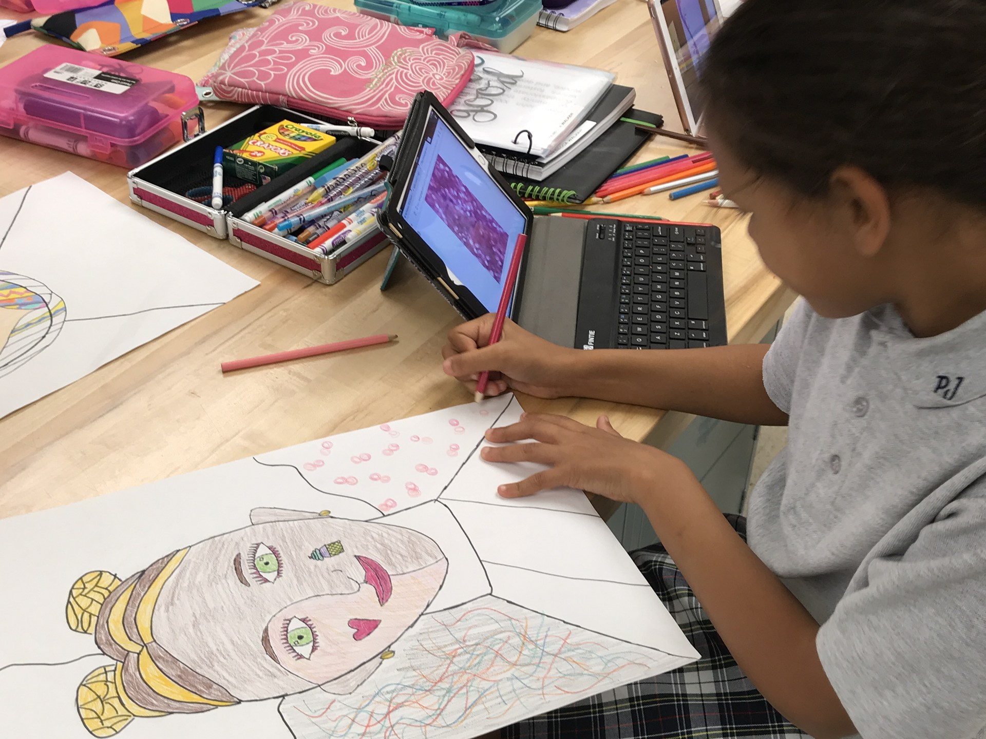 Girl draws picture while looking at iPad
