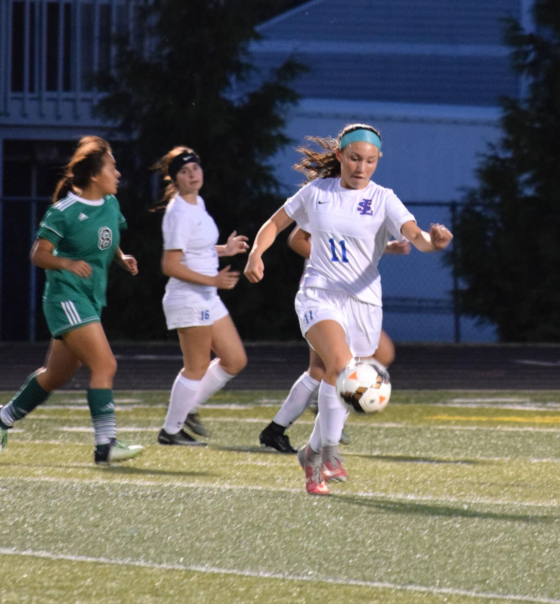 Girl kicking soccer ball.