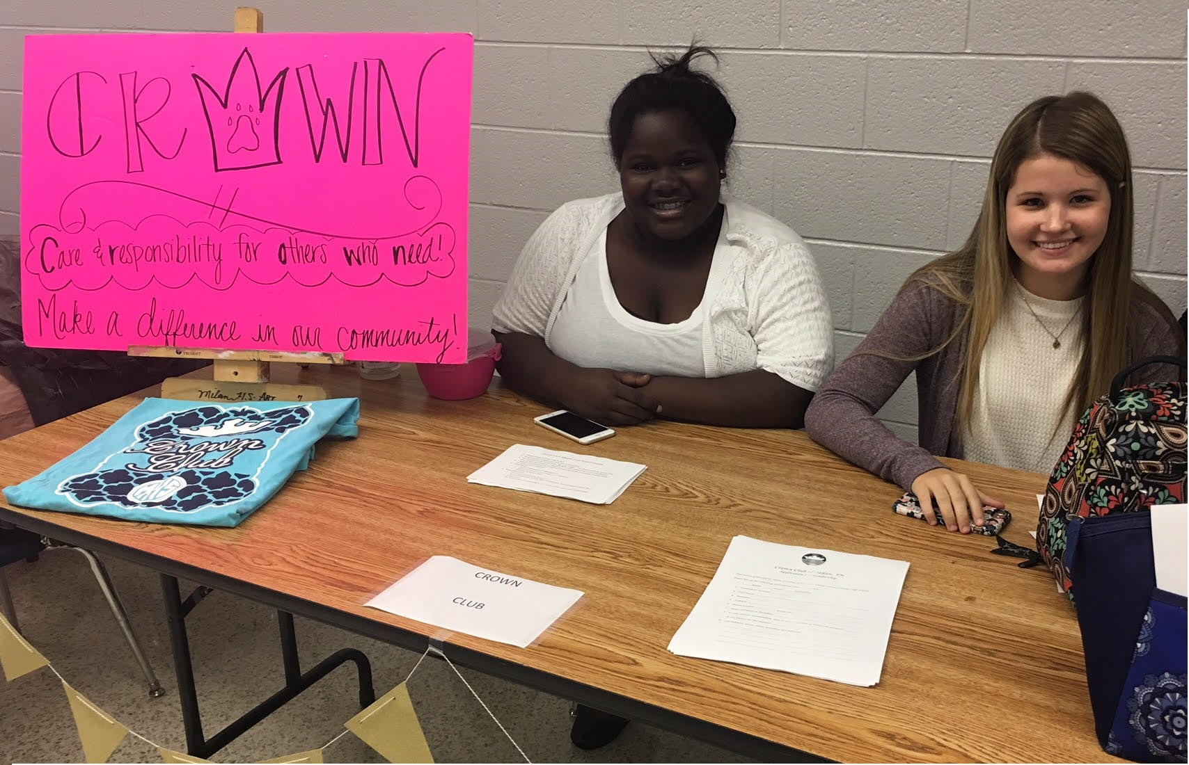 Girls with poster at sign up table