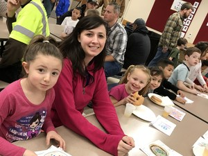 Students and guest celebrating at the kindergarten's Donuts for Dads event.