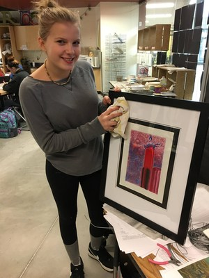 A TKHS student prepares her artwork to hang in offices in the village.