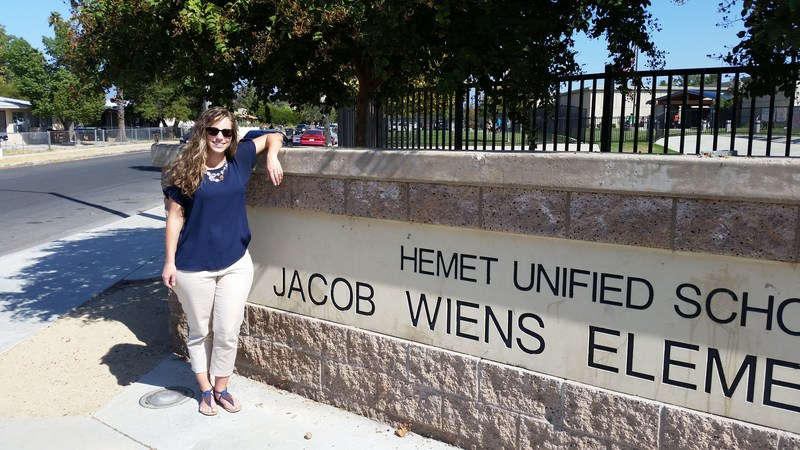 Emily Marzullo in front of a Jacob Wiens sign.