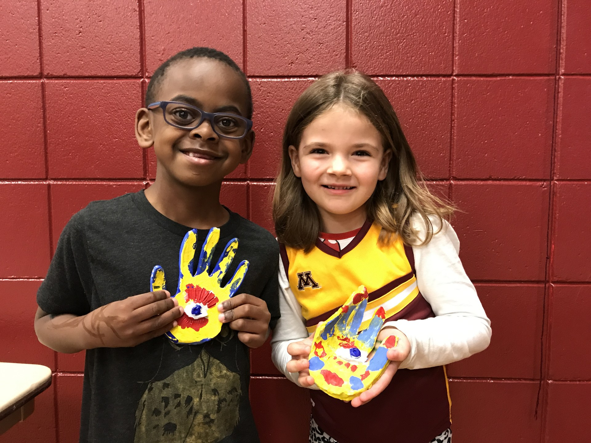 Students holding up a hand art piece.