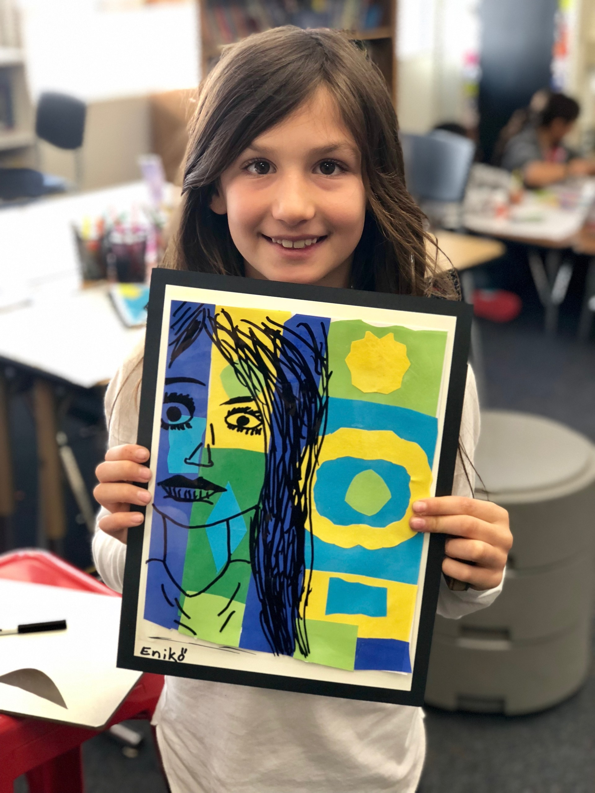 A girl showing her self-portrait with markers on a colorful background.