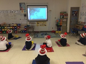 Students watching Dr. Suess in hats