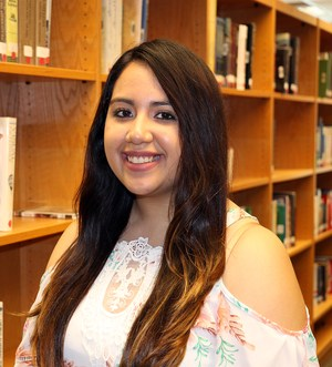Photo of Alyssa Garza in front of a bookcase in library