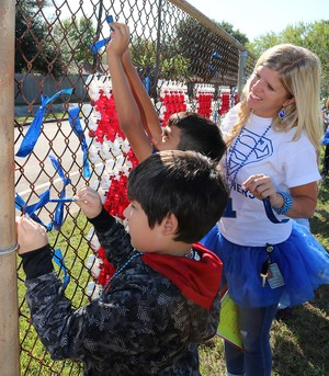 Teacher helping student tie blue ribbon to chain link fence