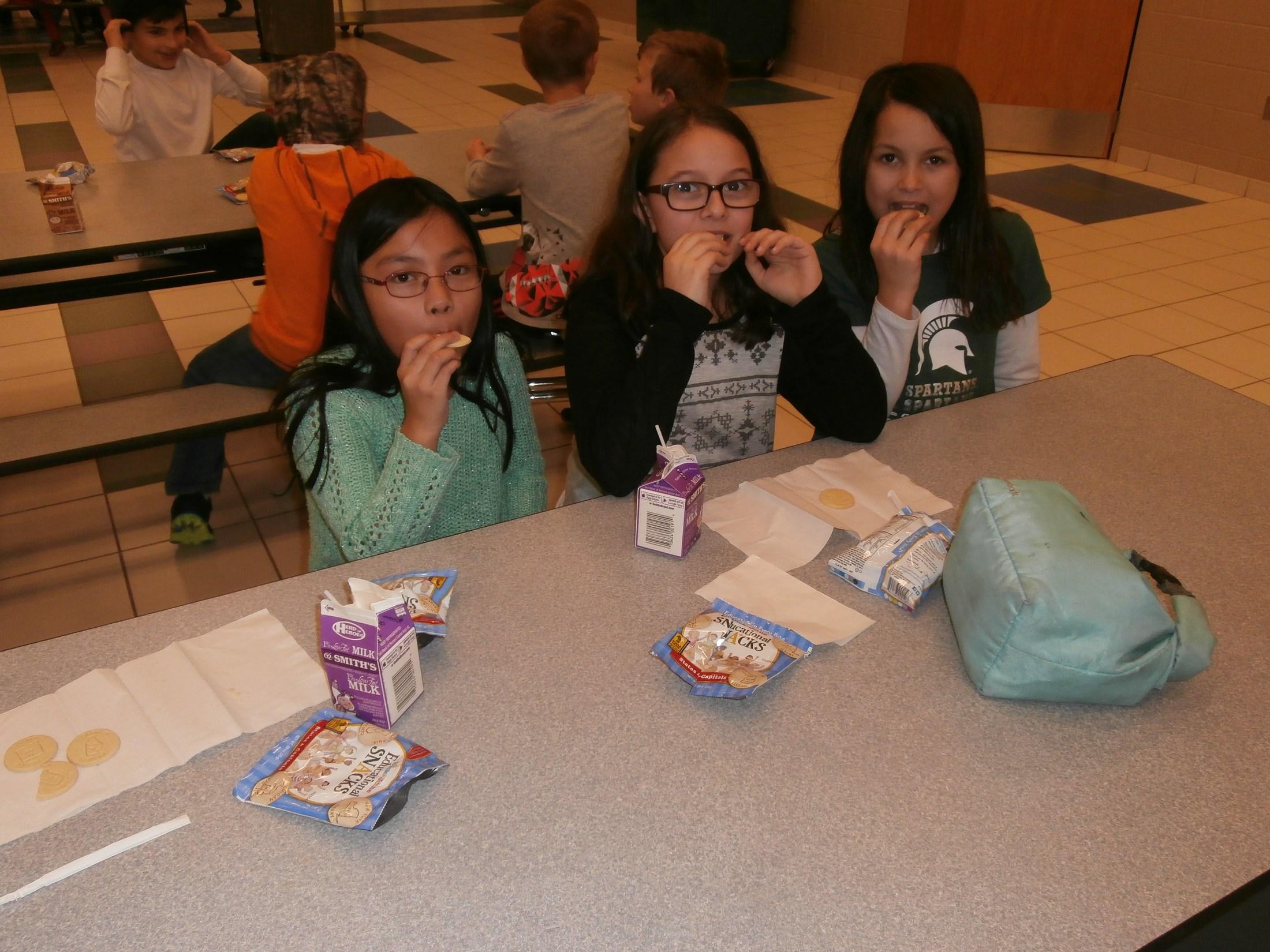Three girls eating snack.