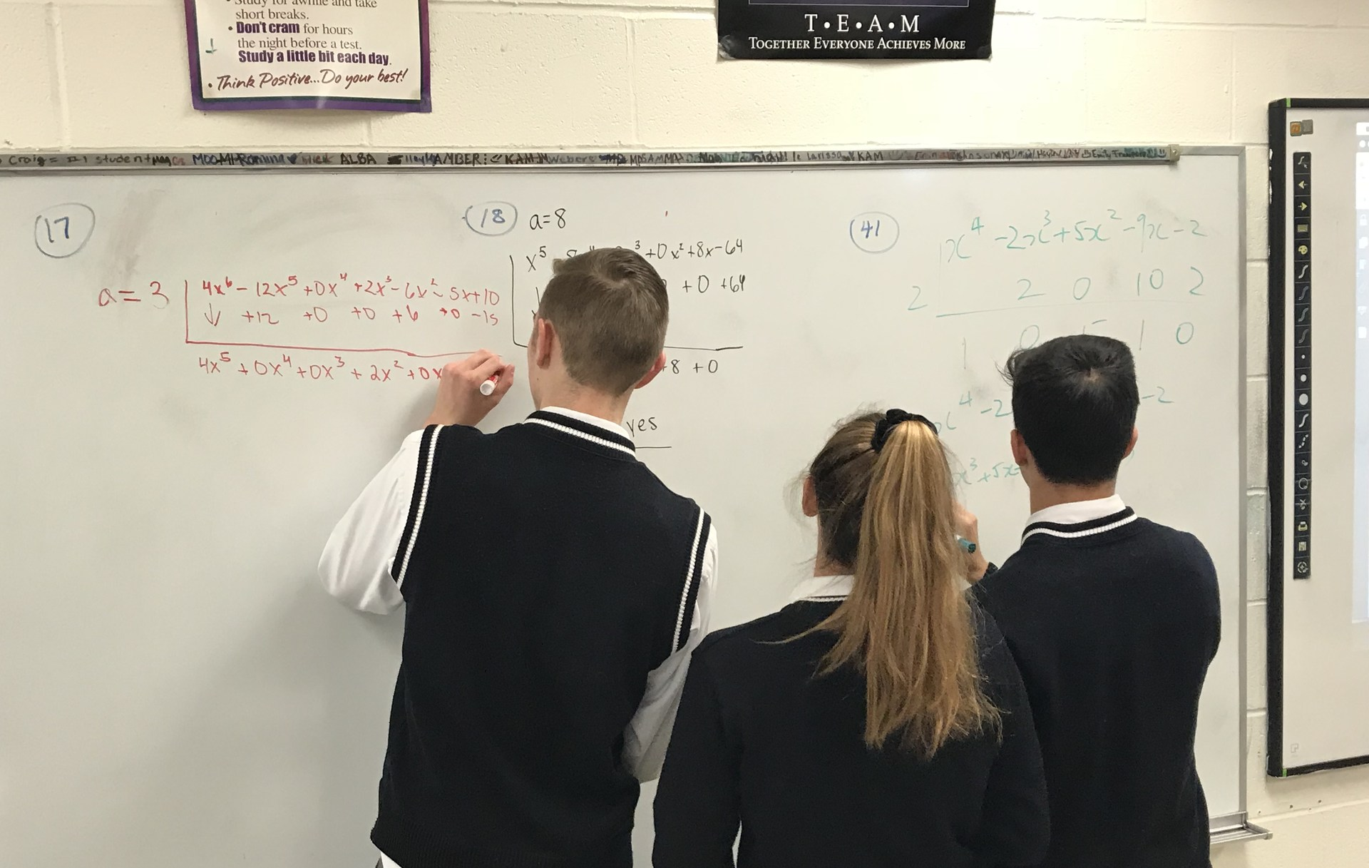 Students writing math problems on board