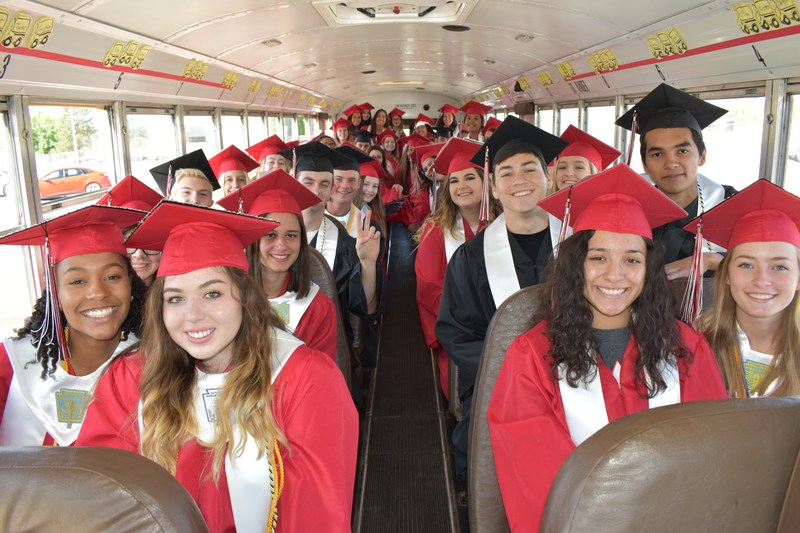 graduating class of 2017 on a school bus before senior strolls
