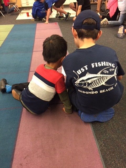 A fifth grade student reads with a kindergarten student.