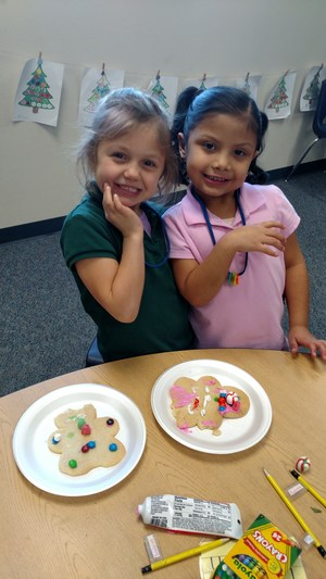 Two girls decorating cookies.