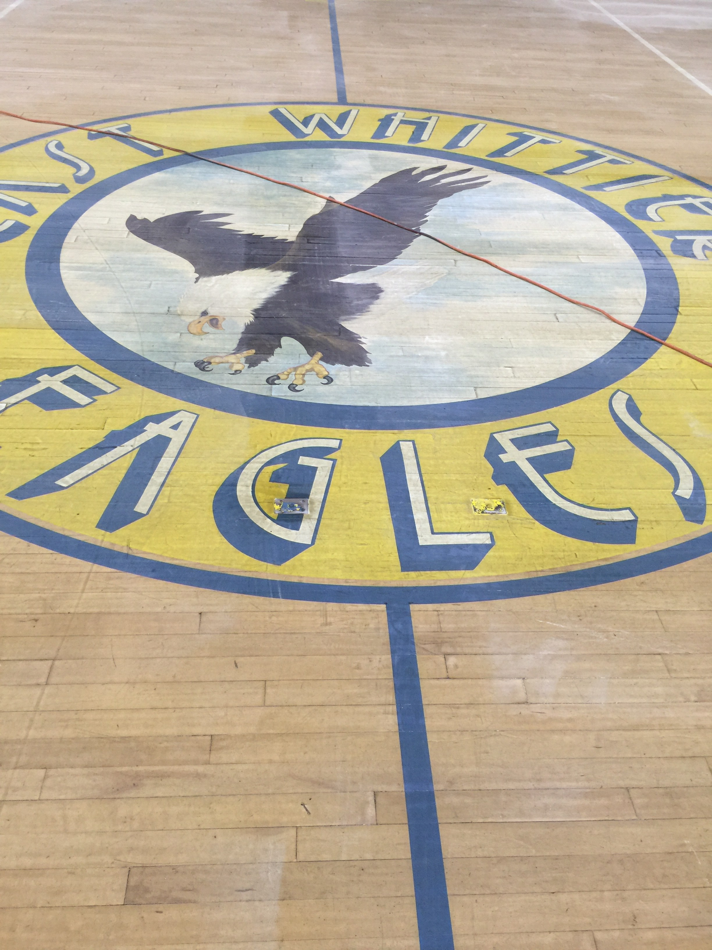 East Whittier Middle School logo on gym floor prior to waxing.