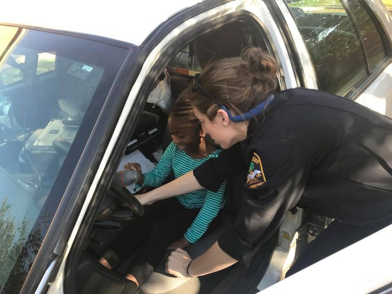 Police officer showing student how to turn on lights in police car.
